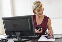使用技术的女实业家在计算机书桌 免版税库存照片