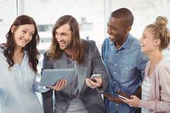使用技术的愉快的企业队 免版税库存图片