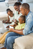 使用技术的愉快的家庭一起 库存图片