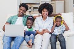 使用技术的愉快的家庭在长沙发 免版税库存照片
