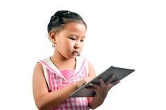 使用技术的逗人喜爱的小女孩 免版税图库摄影