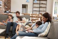 使用技术,家庭坐沙发在开放学制休息室 免版税库存图片