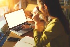 使用技术,有黑发和黄色毛线衣的美丽的女商人在coworking工作在咖啡馆户内 图库摄影