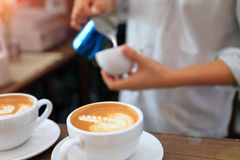 使用投手的Barista倾吐的牛奶的到咖啡拿铁 图库摄影