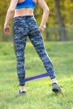 使用抵抗带的体育妇女在她的锻炼 害怕表面女孩纵向惊奇的年轻人 库存图片