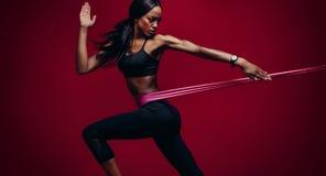 使用抵抗带的坚强的妇女在她的锻炼惯例 库存图片