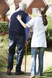 使用拐棍,帮助老人的护工在庭院里走 库存图片