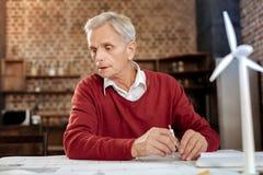 使用指南针的灰发的人描绘图纸 免版税图库摄影