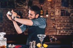 使用振动器的愉快的男服务员为鸡尾酒准备 做龙舌兰酒的男服务员画象在地方客栈根据玛格丽塔酒 免版税库存照片
