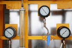 使用措施的压力表压力在生产过程中 工作者或操作员监视由测量仪的油和煤气过程 免版税图库摄影