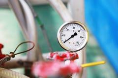 使用措施的压力表压力在生产过程中 工作者或操作员监视由测量仪的油和煤气过程 图库摄影