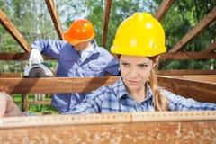 使用措施磁带的建筑师在建造场所 免版税库存照片