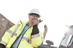 使用携带无线电话的微笑的监督员在建造场所反对清楚的天空 库存图片