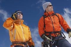 使用携带无线电话的爬山者由朋友 免版税库存图片