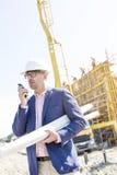 使用携带无线电话的监督员,当举行在建造场所时计划 免版税库存图片