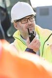 使用携带无线电话的确信的监督员在建造场所 免版税库存照片
