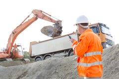 使用携带无线电话的建筑师侧视图,当工作在建造场所时 免版税库存照片