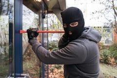 使用撬杠的人打开玻璃门 图库摄影