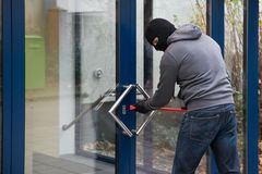 使用撬杠的人打开玻璃门 库存图片