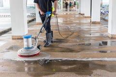 使用擦亮的machi的工作者清洁沙子洗涤外部走道 免版税图库摄影