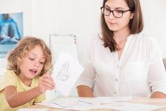 使用支柱的孩子教育治疗师在与一个孩子的一次会议期间与问题 免版税图库摄影
