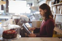 使用收款机的年轻侍者侧视图在咖啡店 库存图片