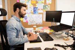 使用数字化器和铁笔在创造性的办公桌上的设计师 库存照片