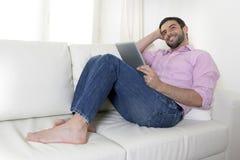 使用数字式垫或片剂的年轻愉快的可爱的人坐长沙发 免版税库存图片