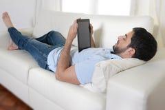 使用数字式垫或片剂的年轻愉快的可爱的人坐长沙发 免版税库存照片