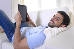 使用数字式垫或片剂的年轻愉快的可爱的人坐长沙发 免版税图库摄影