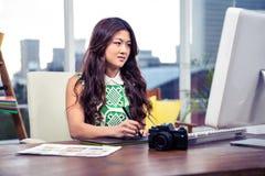 使用数字式委员会和计算机的被聚焦的亚裔妇女 免版税库存图片