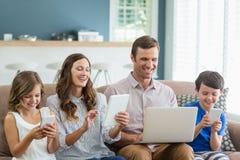 使用数字式片剂、电话和膝上型计算机的微笑的家庭在客厅 免版税图库摄影