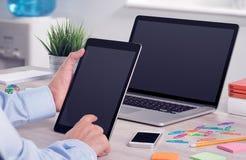 使用数字式片剂个人计算机和膝上型计算机的商人在办公桌上 免版税库存图片