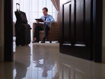 使用数字式片剂个人计算机的生意人在旅馆客房 库存图片