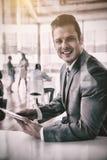 使用数字式片剂办公室的微笑的商人 免版税库存照片