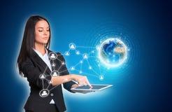 使用数字式片剂和地球与网络的妇女 免版税库存图片