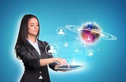 使用数字式片剂和地球与网络的妇女 免版税图库摄影