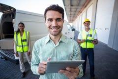 使用数字式片剂和工作者的经理画象站立在背景 免版税库存图片