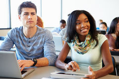 使用数字式片剂和膝上型计算机的大学生在类 免版税库存图片