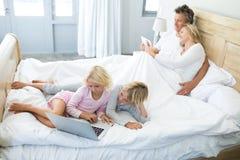 使用数字式片剂和膝上型计算机的家庭在床上在床屋子 库存照片