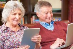 使用数字式片剂和膝上型计算机的资深夫妇在家 库存照片
