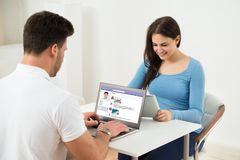 使用数字式片剂和膝上型计算机的年轻夫妇 图库摄影