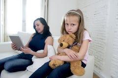 使用数字式片剂垫的年轻互联网上瘾者母亲忽略小哀伤的女儿 库存图片
