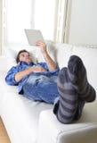 使用数字式片剂垫的年轻可爱的30s人在家说谎在看起来长沙发的网络放松 免版税图库摄影
