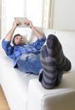 使用数字式片剂垫的年轻可爱的30s人在家说谎在看起来长沙发的网络放松 图库摄影