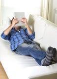 使用数字式片剂垫的年轻可爱的30s人在家说谎在看起来长沙发的网络放松 库存照片