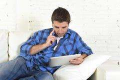 使用数字式片剂垫的年轻可爱的30s人在家说谎在看起来长沙发的网络放松 免版税库存照片