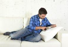 使用数字式片剂垫的年轻可爱的30s人在家说谎在看起来长沙发的网络放松 免版税库存图片