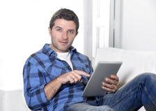 使用数字式片剂垫的年轻可爱的30s人在家说谎在长沙发看起来客厅的网络放松和愉快 库存照片