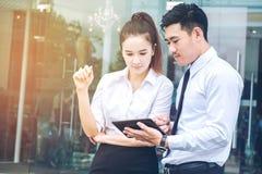 使用数字式片剂室外立场的亚洲企业夫妇会议 免版税图库摄影